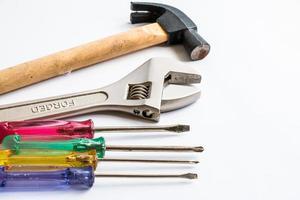 marteau, tournevis et clé sur le fond blanc photo