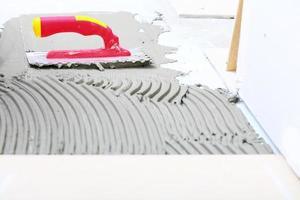 truelle crantée avec mortier pour travaux de carrelage photo