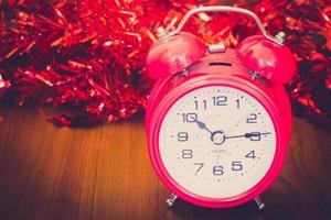 réveil rouge avec deux cloches sur le fond en bois. photo