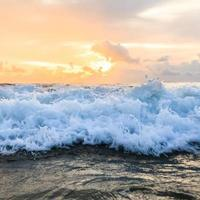 vague de la mer et coucher de soleil photo