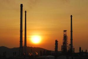 coucher de soleil derrière une raffinerie de pétrole