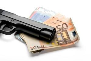 tas de billets en euros avec une arme à feu photo