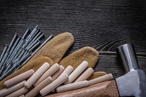 gants en cuir inoxydable construction clous griffe marteau en bois d photo