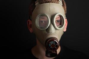 homme avec masque à gaz sur fond noir photo