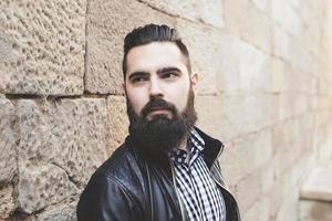 Gros plan du jeune homme barbu moderne appuyé contre le mur. photo