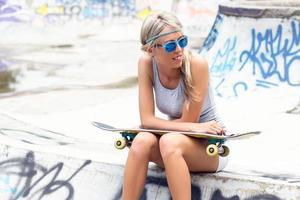 jeune fille avec planche à roulettes assis dans skatepark photo
