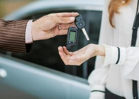 main mâle donnant la clé de la voiture à la main féminine. photo