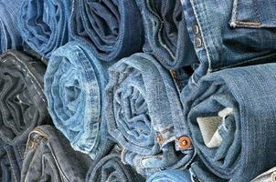 pile de jeans colorés roulés. vue de côté photo