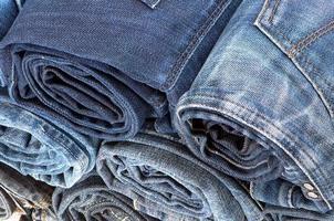 pile de jeans colorés roulés. vue de dessus photo