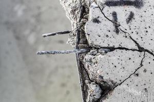 tiges d'acier dépassant du béton fissuré