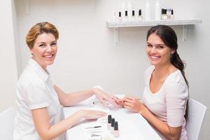 technicienne des ongles donnant au client une manucure photo