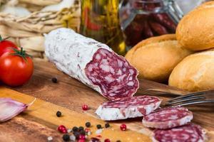 salami en tranches et fourchette à bord photo