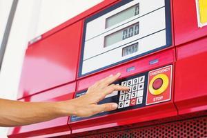 main en appuyant sur les boutons sur une machine de recharge de carburant photo