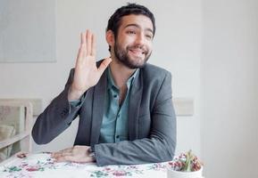 jeune homme portant une veste assis dans un restaurant et appelant serveur. photo
