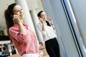 belles femmes utilisant des téléphones et talkin pendant la pause photo