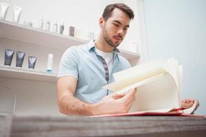 coiffeur souriant avec livre de stock photo