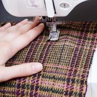 main et pied de machine à coudre sur tissu de laine photo
