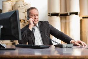 directeur d'entrepôt à l'aide d'un téléphone et d'un ordinateur portable photo