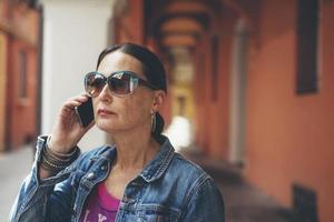 femme appelante avec des lunettes de soleil dans les rues de bologne, en italie. photo