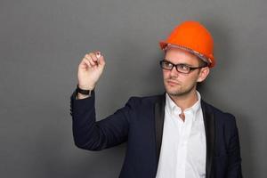 jeune homme d'affaires porte un casque de sécurité, écrit photo