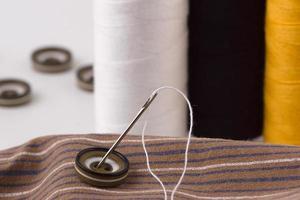 boutons avec un fil et une aiguille