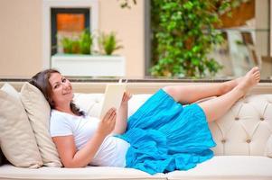 brune sur un canapé blanc, lisant un livre photo