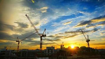 paysage industriel avec des silhouettes de grues sur le coucher du soleil ba