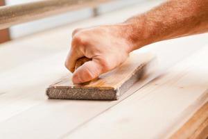 lissage du bois à la main avec une ponceuse à bande