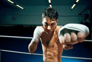 un jeune homme boxe dans un ring de boxe photo