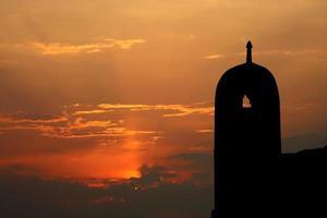 coucher de soleil près des ruines de l'ancienne tour de la mosquée photo