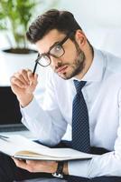 bel homme d'affaires réfléchi à lunettes assis sur le lit avec journal photo