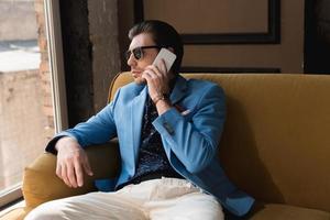 élégant jeune homme parlant par téléphone tout en étant assis sur le canapé photo
