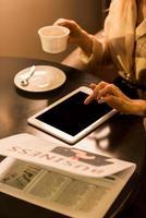 Photo recadrée de femme d'affaires avec une tasse de café à l'aide d'une tablette avec écran blanc au café