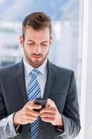 beau jeune homme d'affaires messagerie texte photo