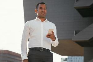 homme d'affaires pensif avec téléphone portable à l'extérieur photo