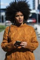 Portrait de jolie femme afro à l'aide de téléphone portable dans la rue photo