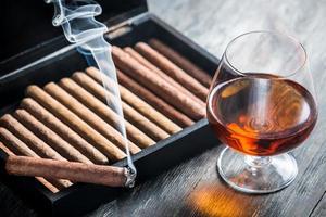 cigare brûlant et cognac en verre photo