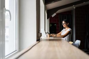 recherche de nouvelle solution. pensive jeune belle femme d'affaires dans des verres travaillant sur ordinateur portable tout en étant assis sur son lieu de travail photo