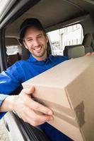 chauffeur-livreur détenant un colis dans sa camionnette photo