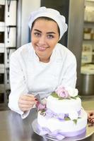 boulanger décore un gâteau avec un colorant alimentaire photo