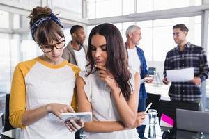 collègues féminines utilisant ensemble le numérique photo