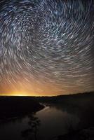 beau ciel nocturne, traînées d'étoiles en spirale et forêt photo