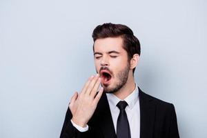 Close up portrait de s'ennuyer dans des vêtements formels homme bâillant isolé sur fond gris