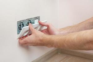 les mains d'un électricien installant une prise murale photo