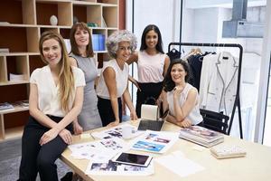 Toute l'équipe créative féminine souriant à la caméra dans un bureau