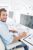 Vue de côté portrait d'un éditeur de photos masculin travaillant sur ordinateur