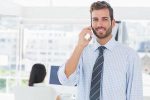 artiste masculin à l'aide de téléphone portable avec un collègue en arrière-plan photo