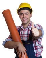 Heureux travailleur de la construction hispanique avec tuyau d'eau montrant le pouce
