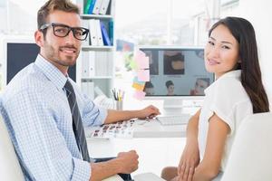 vue arrière des éditeurs de photos occasionnels travaillant sur ordinateur