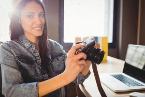 graphiste regardant des photos dans un appareil photo numérique